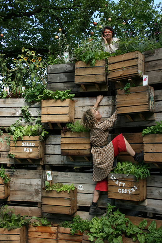 Tanja Beer's The Living Stage with performer Penny Baron climbing up the apple crate walls.